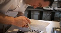 Stubbe Chocolates owner Daniel Stubbe uses a piping bag filled with tempered chocolate to trace the outline of a template design in milk chocolate.