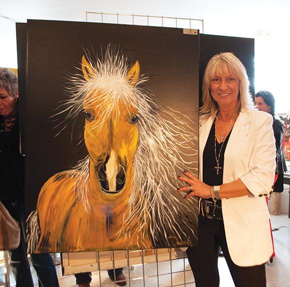 "Artist Renata Dusk with one of her creations: ""Fire."" (Kenya Bruce/Toronto Observer)"