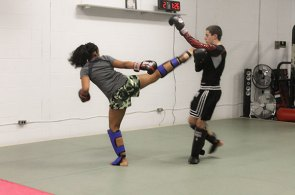 Students at Team UMAC MMA & Fitness learn how to deliver and protect against sidekicks.