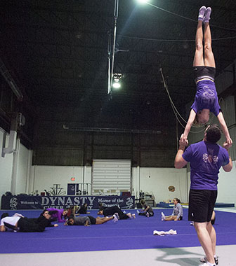 """Travis Stirrat demonstrating a skill. He has 14 years of experience. Dynasty Cheer Academy to him is a, """"combination between sports acrobatics, power tumbling, gymnastics, trampoline,"""" he said."""