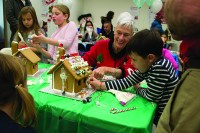 Tillie Lewis, in red, and her grandson Oliver, 5, decorating their gingerbread house.
