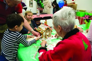 Three-year-old Amelia Lewis, centre, decorates a gingerbread house at Habitat for Humanity's Gingerbread Build with her grandfather David, brother Oliver, 5, and grandmother Tillie.