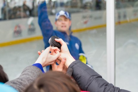 Assistant Coach Scott Gordon throwing out pucks to the crowd.