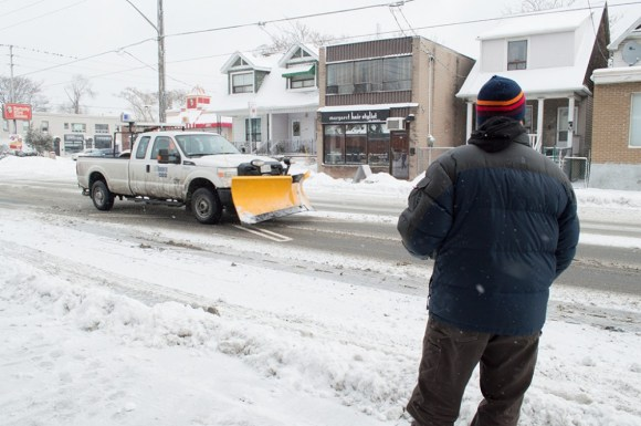 A snow truck drives by a bus stop after yet another snow storm.