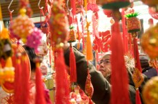 A shopper takes a look at hanging ornaments and pendants. Chinatown is bathed in red and gold decorations, especially during this season, as the two colours are said to be auspicious.