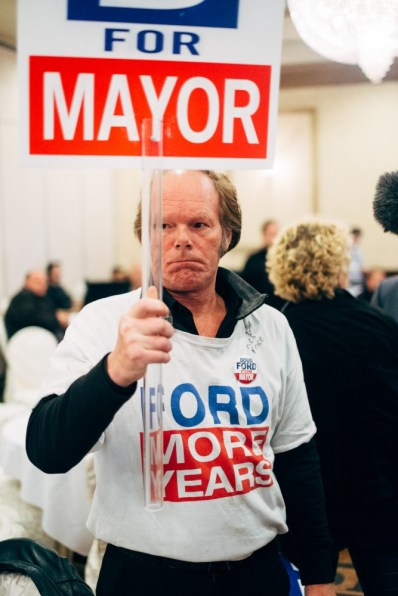 Doug Ford supporter holds his sign as both Ford's leave the hall