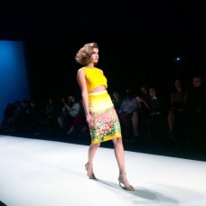 The Spring 2015 collection by Rachel Sin saw many floral pieces. Here, a model walks down the runway in a yellow cutout dress.