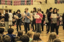 Grade 7 students read their reflections in the form of tweets for the hash-tag #HowIRemember.
