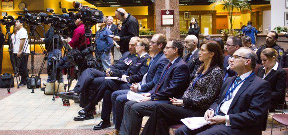 Chief William Blair and President Jennifer Evans, at far left of front row, listen to speeches on crime prevention conducted by community partners.