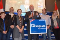 John Carmichael's family and his associates stand by him in good spirits as he gives his concession speech.