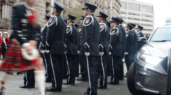 A man wearing the traditional dress of Scotland walks past the men and women of the Toronto Fire Services.