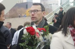 French Consul General Mr. Marc Trouyet holds flowers that attendees gave him.