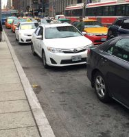 Double-parked taxis outside city hall cause major delays during the morning and evening rush