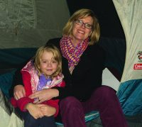 Event organizer Elizabeth Dove and daughter sit in tent prepared to spend a night sleeping outdoors to raise money for Syrian refugees.