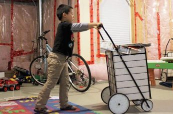 Six-year-old Joshua shows off the cart he uses to deliver papers with the help of his mom.