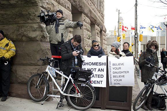 Two demonstrators setting up just outside the north entrance of Old City Hall, where Jian Ghomeshi entered his third day of trial.