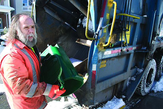 Toronto waste collector, Henry Mullet, works his way along Ferrier Avenue following Tuesday's snowstorm.