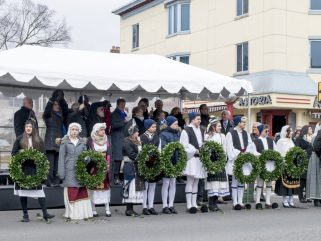 Volunteers hold wreaths during the parade in anticipation of the wreath-laying ceremony.