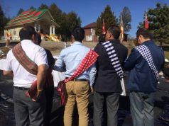 Men wear traditional sashes as part of the cultural attire.