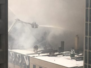 Fire truck ladder sprays water onto roof of building