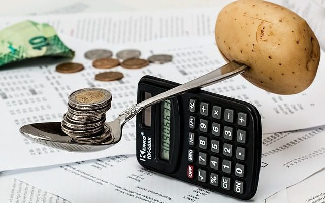 Potato balancing out coins on calculator
