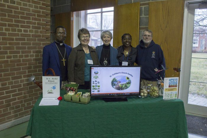 From left to right, Rev. Ian LaFlueur, Kathi Davies, Nancy Wahlroth, Lorraine Green LaFleur and Bob Davies stand at a table with information about the vegetable garden, herb garden and pollinator garden at the environmental fair for St. Chuthburt's Church.