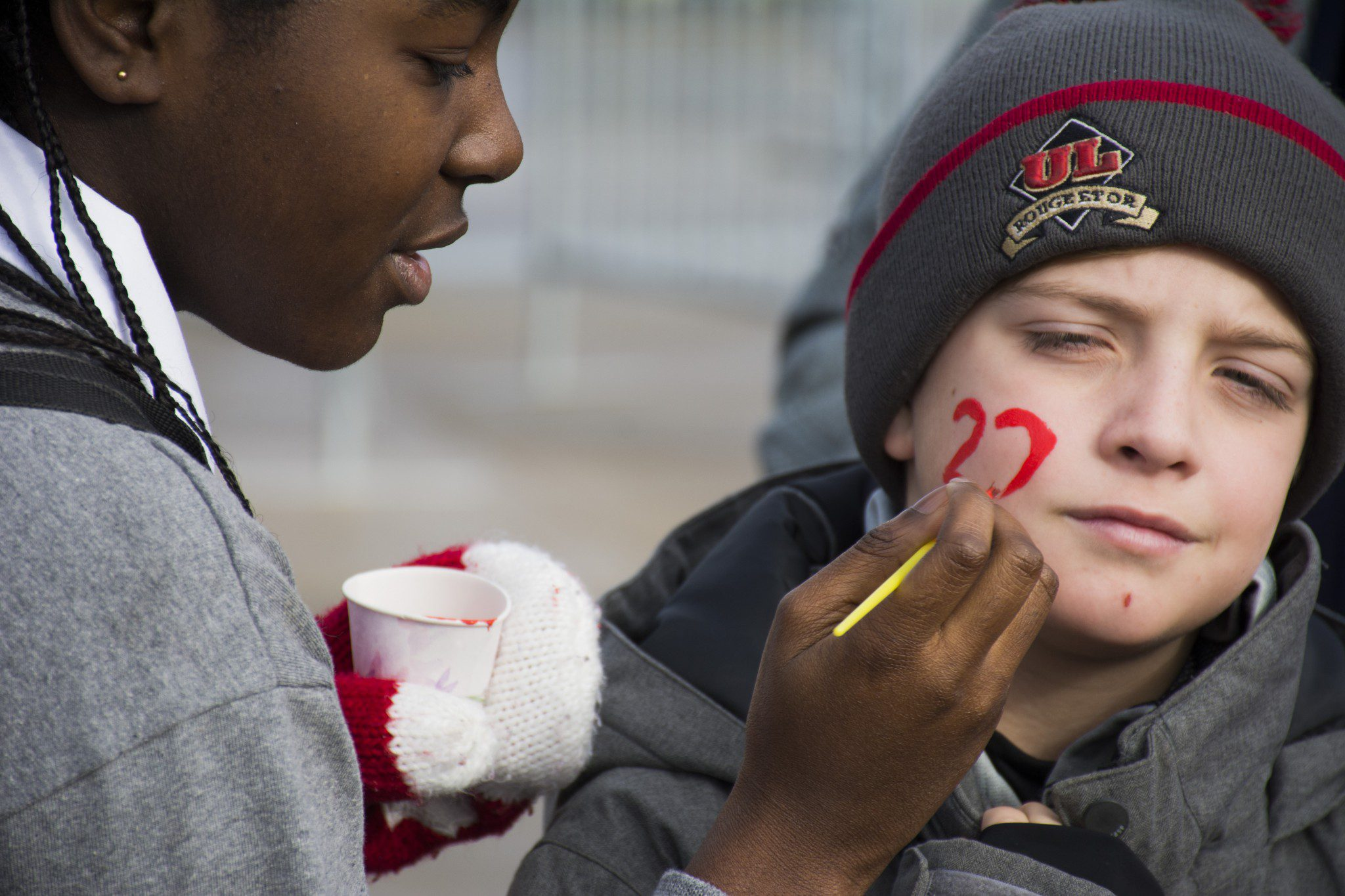 young fan getting his face painted