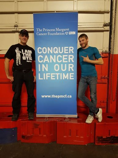 Matthew Hayley and his coach, Shaun de Jager, stand beside a Princess Margaret Cancer Foundation banner.