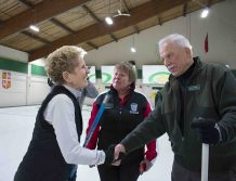 Wynne shakes hands with a curler.