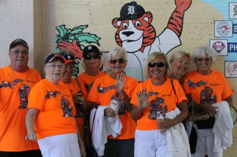 A cheerful group of Detroit Tigers fans pose in front of a Tigers mural while awaiting the game to start. (Nikolas Marsiglio photo)