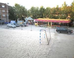 Parking de la Calle Real preparado con la pista de arena y atracciones para las Fiestas de la Asunción en Torrelodones