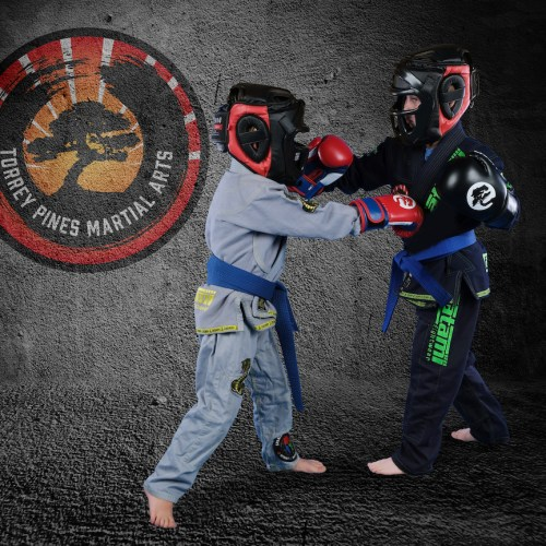 Photo of two kids sparring with safety gear