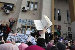 An anti-government protester holds the Muslim holy book, the Koran, while protesters chant anti-government slogans in Benghazi city, Libya, February 23, 2011.