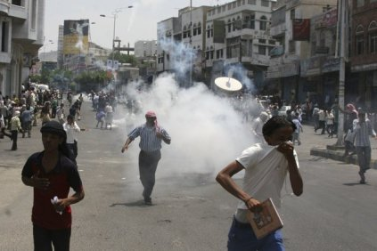 Anti-government protesters demanding the ouster of Yemen's President Ali Abdullah Saleh flee after security forces fired tear gas grenades at them during clashes in the southern city of Taiz September 19, 2011.