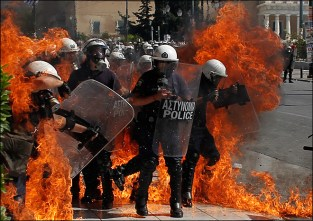 A fire bomb explodes among riot police during clashes in Athens Wednesday Sept. 26, 2012.