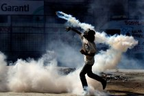A protester throws back to police a tear gas canister during clashes in Taksim square in Istanbul, Tuesday, June 11, 2013. AP Kostas Tsironis