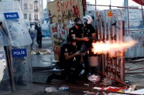 A riot policeman launches a tear gas canister during clashes in Taksim square in Istanbul, Tuesday, June 11, 2013. AP Kostas Tsironis