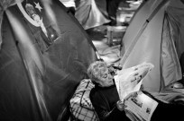 An elderly woman in Gezi Park reads the news. The tent community occupying the park was violently destroyed on June 16th.