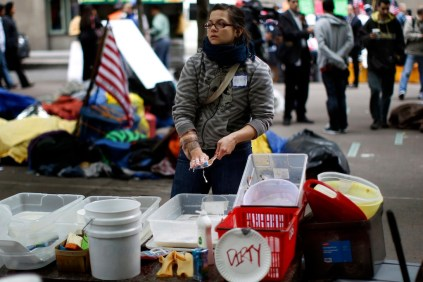 Occupy Wall Street protester washes dishes at the protesters' camp in Zuccotti Park in lower Manhattan in New York