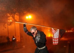 Occupy Oakland protester Mike Clift runs from teargas early Thursday morning, Nov. 3, 2011, in Oakland, Calif