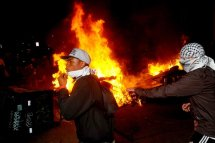Occupy Oakland protesters pass a burning garbage heap during a confrontation with police on Thursday, Nov. 3, 2011, in Oakland, Calif.