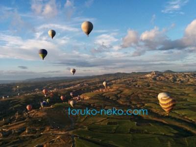 カッパドキア 気球 からの気球の眺め 景色の写真 画像 複数の気球が見えており、下には地面も見えている画像