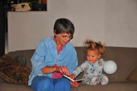 Grandma Nancy reads to Pigtails.