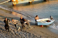 The local lads dragging a boat up the beach