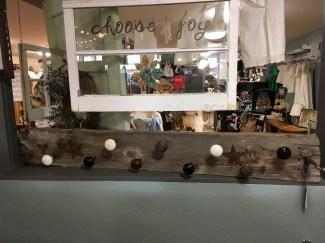 This reclaimed wood coat hanger has eight antique door knobs for hanging coats.