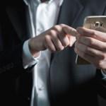 ビジネスマンがスマホでメールを打つ写真
