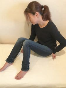 ムズムズ脚症候群・RLSの症状部位を押さえる女性
