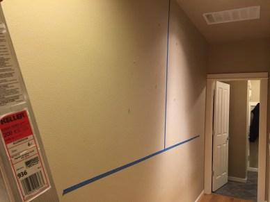A photo of a wall with painters tape to mark off where the wall will go