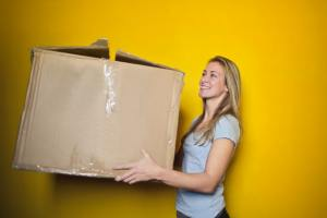 blond woman holding large box and smiling in front of a bright yellow background