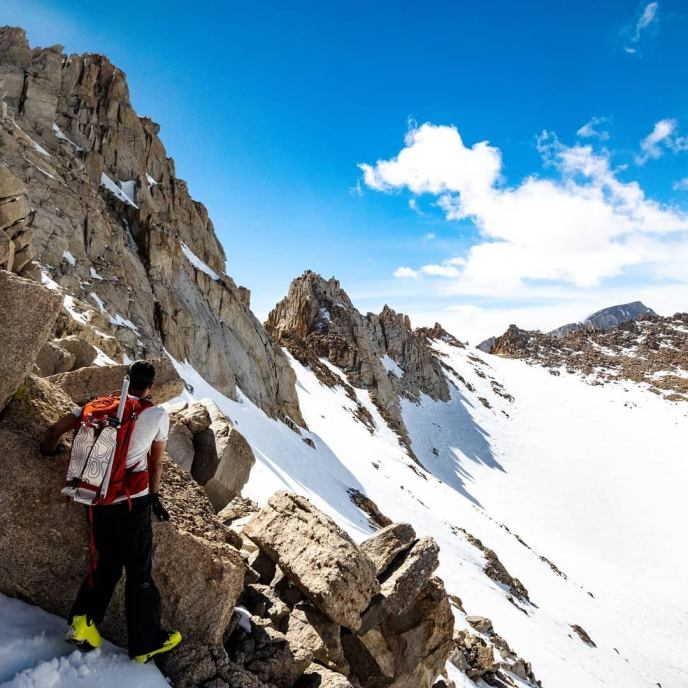 Rafee scopes out the route below Mt Mallory as Mt Whitney's massive summit peers over a 13,500 ft ridgeline.